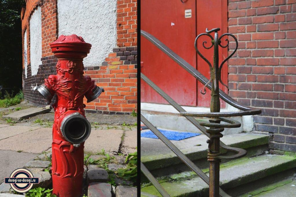 Пожарная колонка и перила около старых немецких домов