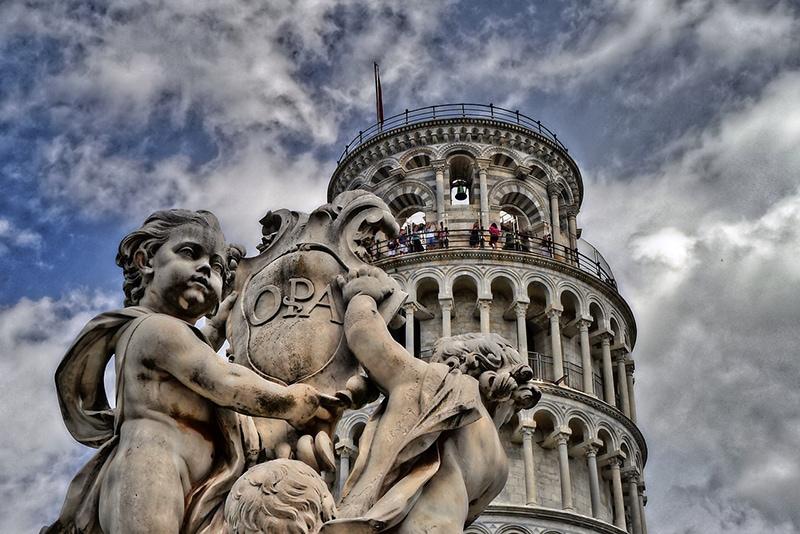 Скульптуры ангелов с фонтана на фоне Падающей башни