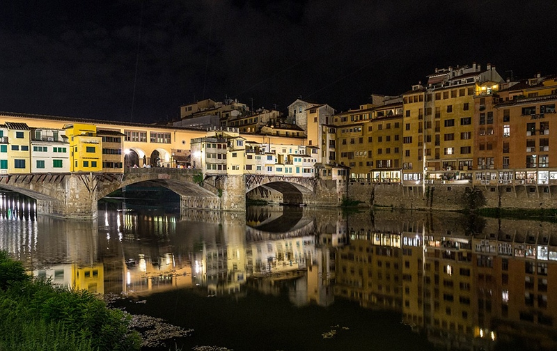 Мост Понте-Веккьо ночью с огнями, отраженными в воде, выглядит еще эффектней, чем днем