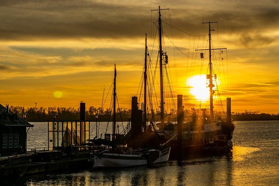 Вдоль набережной стоят старинные здания и многочисленные корабли, пришвартованные у берега