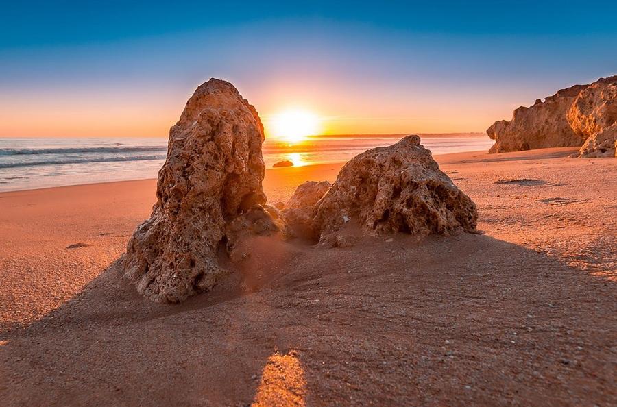 На пляже золотистой песок и огромные валуны, разбросанные по всему побережью