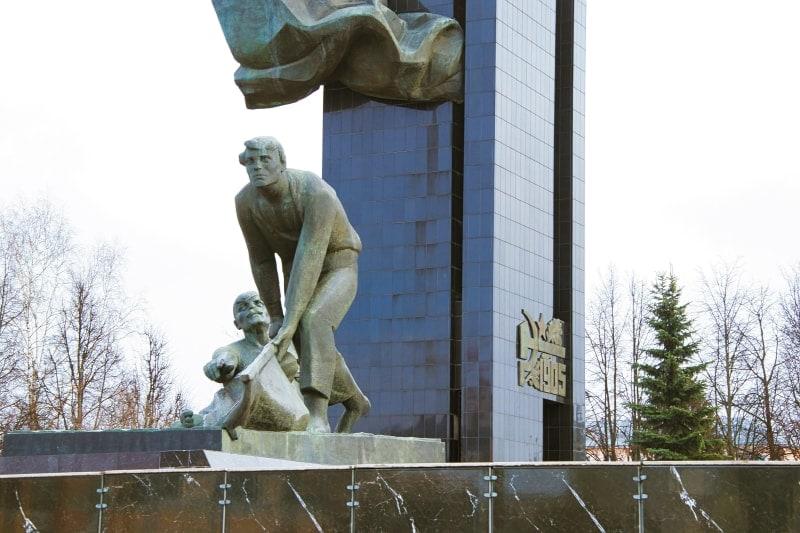Поднимающий знамя на фоне обелиска в городе Иваново