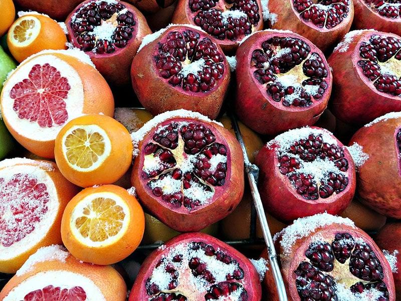 Гранаты и апельсины на рынке в Стамбуле